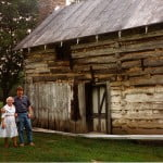 Farrell and his grandmother in front of the school house